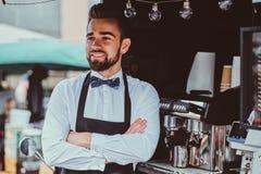 Элегантное barista ждет клиентов на его собственном небольшом coffeeshop стоковое фото