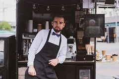 Элегантное barista ждет клиентов на его собственном небольшом coffeeshop стоковые фото