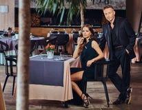 Элегантно одетые пары - красивый стильный мужчина и очаровательная женщина брюнет во время датировка в роскошном ресторане стоковые фотографии rf