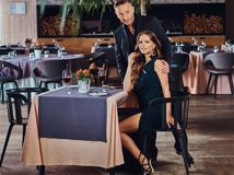 Элегантно одетые пары - красивый стильный мужчина и очаровательная женщина брюнет во время датировка в роскошном ресторане стоковое изображение rf