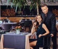 Элегантно одетые пары - красивый стильный мужчина и очаровательная женщина брюнет во время датировка в роскошном ресторане стоковое изображение