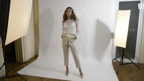 Элегантные актрисы одетые в белый представлять в студии с руками в ее карманн и волосах на одной стороне для фотографа - сток-видео