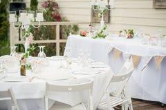Элегантные белые стулья и сервировки стола составляют этот wedding rec стоковые фото