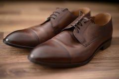 Элегантные, используемые коричневые кожаные мужские ботинки установили на коричневый деревянный стол стоковая фотография rf