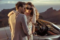 Элегантные любовники представляя рядом с автомобилем с откидным верхом Стоковое Изображение