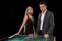 Элегантные пары на казино держа пари на рулетке, на черной предпосылке Стоковые Изображения