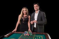 Элегантные пары на казино держа пари на рулетке, на черной предпосылке Стоковые Фотографии RF