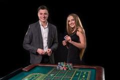 Элегантные пары на казино держа пари на рулетке, на черной предпосылке Стоковое Изображение
