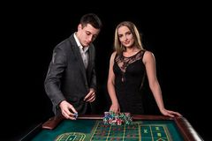 Элегантные пары на казино держа пари на рулетке, на черной предпосылке Стоковые Фото