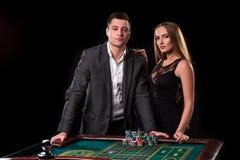 Элегантные пары на казино держа пари на рулетке, на черной предпосылке Стоковое Изображение RF