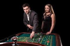 Элегантные пары на казино держа пари на рулетке, на черной предпосылке Стоковая Фотография RF
