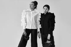 Элегантные пары черных и азиатских женщин в модная черной и Стоковая Фотография