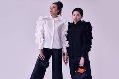 Элегантные пары черных и азиатских женщин в модных черно-белых костюмах Стоковые Фото