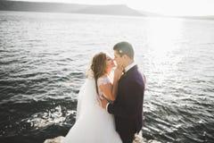 Элегантные стильные счастливые пары свадьбы, невеста, шикарный groom на предпосылке моря и небо Стоковые Фотографии RF