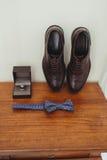 Элегантные стильные темные мужские аксессуары на деревянной предпосылке Взгляд сверху бабочки, ботинок, флористического корсажа,  Стоковое Изображение