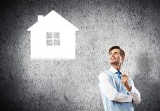 Элегантный банкир нося красную связь и дом подписывают как концепция банка стоковое фото