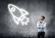 Элегантный банкир нося красный знак связи и ракеты как технология жульничает стоковое фото