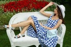 Элегантный, довольно и красивая молодая дама лежащ и представляющ на плетеной софе в природном парке стоковые изображения rf