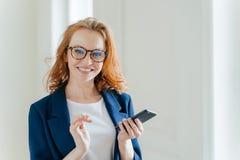 Элегантный женский copywriter с широкой улыбкой ищет информацию статьи и издание на сотовом телефоне носит зрелища стоковые изображения rf