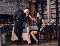 Элегантный и красивый джентльмен целует его любимую руку ` s во время датировка в ресторане стоковая фотография rf