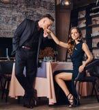 Элегантный и красивый джентльмен целует его любимую руку ` s во время датировка в ресторане стоковая фотография