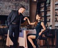 Элегантный и красивый джентльмен целует его любимую руку ` s во время датировка в ресторане стоковое фото rf