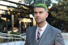 Элегантный красивый человек с зелеными волосами в размерах офиса стоковое фото rf