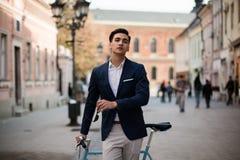 Элегантный молодой человек с велосипедом outdoors на улице Стоковые Изображения