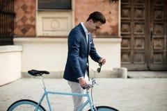 Элегантный молодой человек с велосипедом outdoors на улице Стоковая Фотография