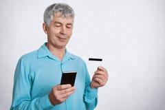 Элегантный мужской пенсионер держит умный телефон и кредитная карточка, проверяет его учет и пенсию в онлайн Веб-странице, удовле стоковые фотографии rf