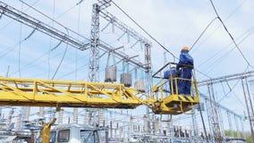 Электрики поднимаются вверх в вашгерд крана смертной казни через повешение к линиям электропередач видеоматериал