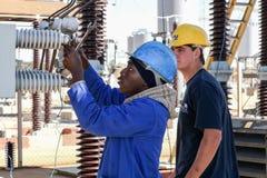 Электрики работая на высоковольтных линиях электропередач Стоковые Изображения