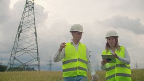 Электрик в полях около линии передачи энергии Электрик управляет процессом раскрывать силу сток-видео