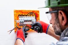 Электрик на работе на электрической панели стоковые фото