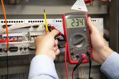 Электрик регулирует щиток управления системой электропитания стоковые фотографии rf