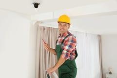 Электрик с отверткой ремонтируя камеру CCTV стоковые фото