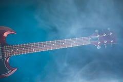 Электрическая гитара в дыме, голубой предпосылке Стоковые Фото