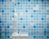 Электрическая зубная щетка на голубой предпосылке плитки Стоковое фото RF