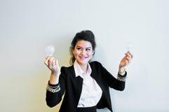Электрическая лампочка владением бизнес-леди на белой предпосылке Стоковые Изображения RF
