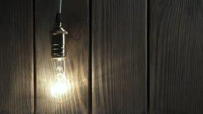 Электрическая лампочка медленно освещает вверх, быстро фликеры на предпосылке от древесины сток-видео