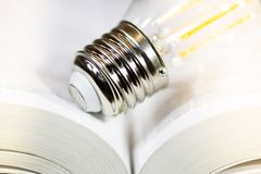 Электрическая лампочка на книге стоковое фото rf