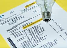 Электрическая лампочка на счете за электричество стоковые фото