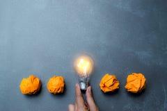 Электрическая лампочка положила в середине оранжевых бумаг ее для идеи, энергии Стоковая Фотография