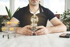 Электрическая лампочка руки человека с монетками стоковое изображение rf