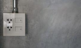 Электрическая штепсельная вилка и переключатель на серой стене Стоковые Изображения