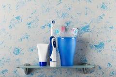 Электрические и ручные зубные щетки в стекле, зубной пасте, на полке Стоковое Фото