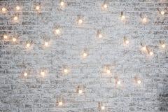 Электрические лампочки на белой предпосылке кирпича Винтажная гирлянда электрических лампочек edison в интерьере просторной кварт Стоковое Изображение RF