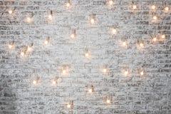 Электрические лампочки на белой предпосылке кирпича Винтажная гирлянда электрических лампочек edison в интерьере просторной кварт Стоковые Фотографии RF