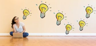 Электрические лампочки при молодая женщина используя портативный компьютер Стоковое Изображение RF