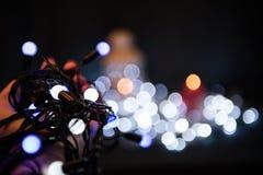 Электрические лампочки рождества в руках Стоковая Фотография